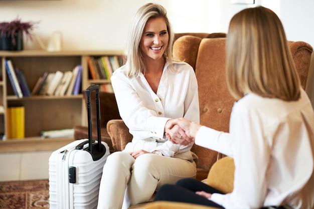 Dwie kobiety biznesu ściskają sobie ręce w nowoczesnym hotelowym foyer