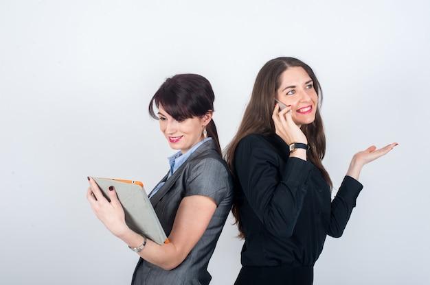 Dwie kobiety biznesu stojące plecami do siebie i uśmiechnięte