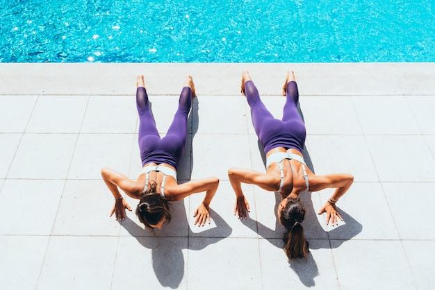 Dwie kobiety bliźniaczki robi ćwiczenia gimnastyczne przy basenie