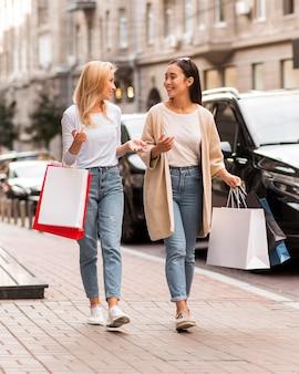 Dwie kobiety chodzą po ulicy, trzymając torby na zakupy