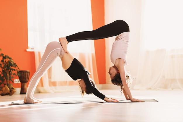 Dwie kobiety ćwiczą jogę, jedna wykonuje ćwiczenia psa skierowanego w dół, a druga róg z nogami spoczywającymi na dolnej części pleców adho mukha shvanasana