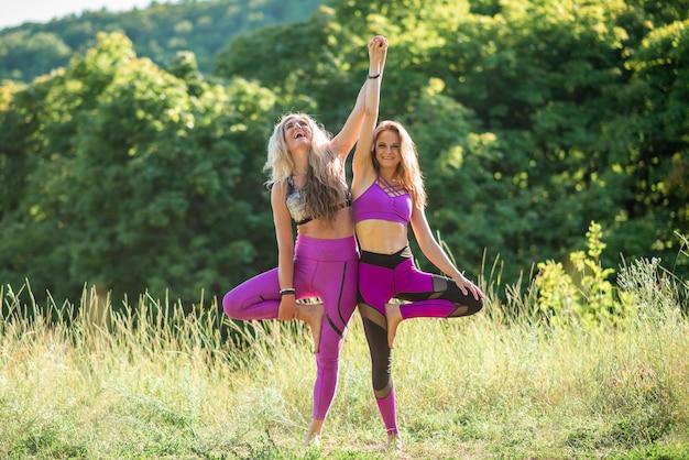 Dwie kobiety ćwiczą jogę w przyrodzie w słoneczny dzień