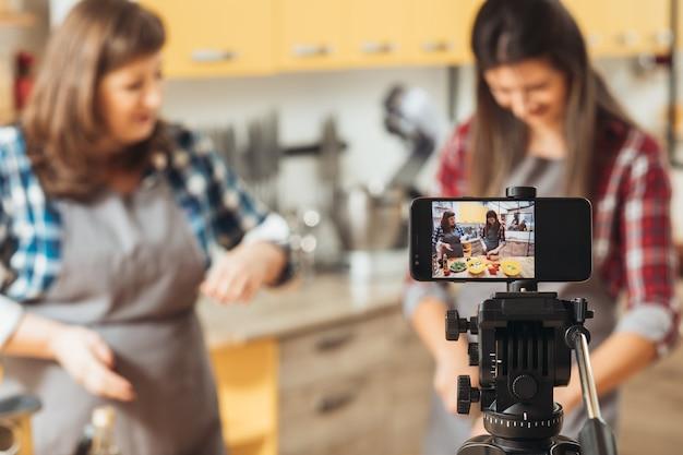 Dwie kobiety filmowanie procesu gotowania na smartfonie