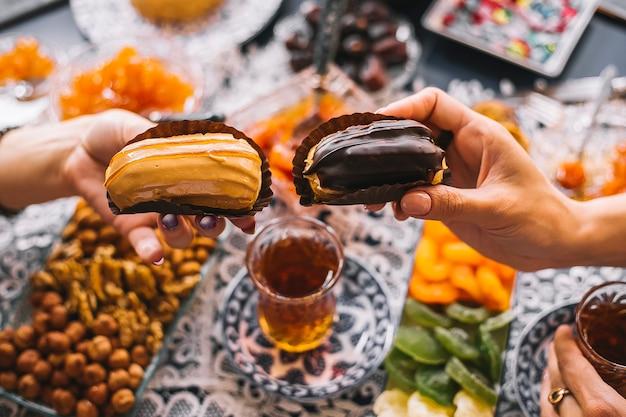 Dwie kobiety gospodarstwa karmelowe i czekoladowe eklery