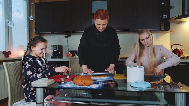 Dwie kobiety i młoda dziewczyna robi przygotowania do pieczenia ciasteczek w kuchni