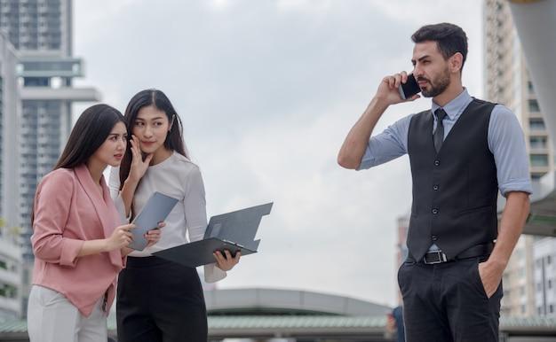 Dwie kobiety interesują się plotkować szef lub biznesmeni