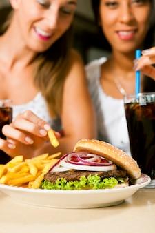 Dwie kobiety je hamburgera i pije sodę