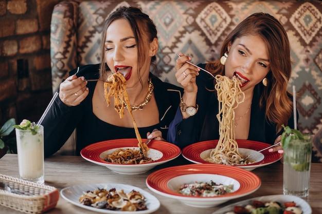 Dwie kobiety jedzą makaron we włoskiej restauracji