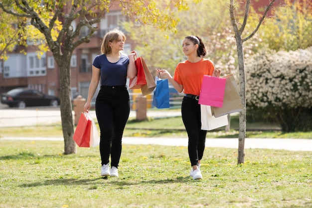 Dwie kobiety latina spaceru w parku w słoneczny dzień z torbami na zakupy