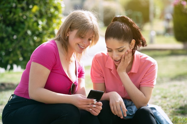 Dwie kobiety latina w parku patrząc na telefon komórkowy w słoneczny dzień