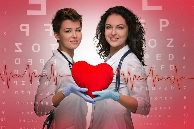 Dwie kobiety lekarz trzymający czerwone serce na czerwonym tle stołu okulistycznego