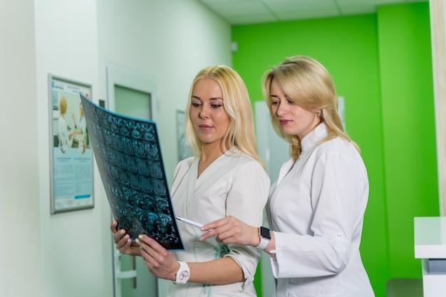 Dwie kobiety lekarze medycyny patrząc na zdjęcia rentgenowskie w szpitalu. koncepcja neurochirurgii.