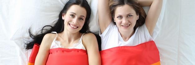 Dwie kobiety leżące w łóżku pod flagą lgbt widok z góry koncepcja miłości tej samej płci