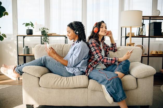 Dwie kobiety lubią słuchać muzyki siedząc plecami do siebie.