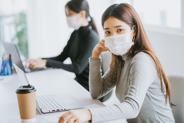 Dwie kobiety muszą nosić maski w godzinach pracy, aby zachować bezpieczeństwo podczas epidemii