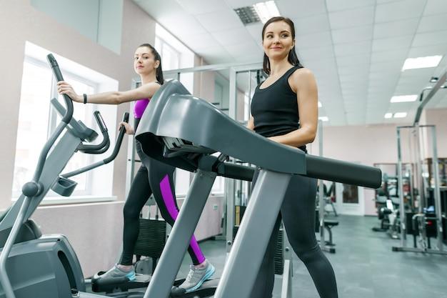 Dwie kobiety na bieżni w nowoczesnej siłowni sportu