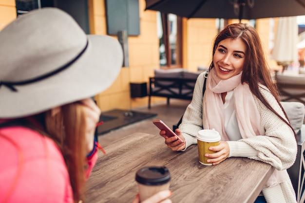 Dwie kobiety na czacie, mając kawę w kawiarni na świeżym powietrzu. szczęśliwi przyjaciele za pomocą telefonu. dziewczyny spędzają czas