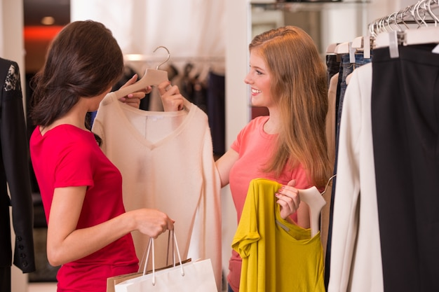 Dwie kobiety na zakupy wybierając sukienki