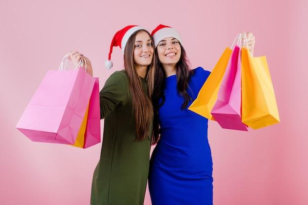 Dwie kobiety noszące czapki mikołaja z kolorowymi wakacyjnymi torbami na zakupy odizolowywającymi nad menchiami