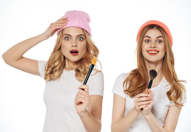 Dwie kobiety noszące czapki, trzymając pędzle do makijażu