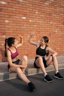 Dwie kobiety po miejskim treningu dają piątkę za świetne wyniki. dziewczyny przygotowujące się do biegania i siedzące na ulicy.