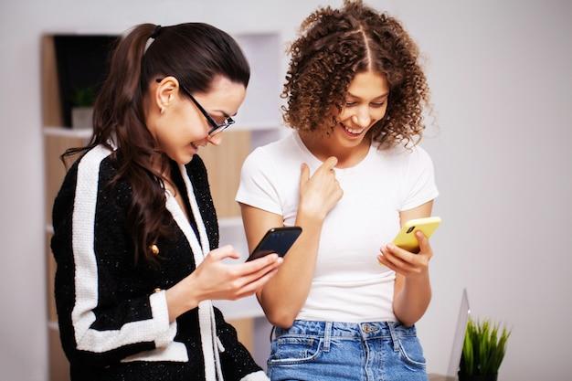 Dwie kobiety pracują razem w biurze nad wspólnym projektem.