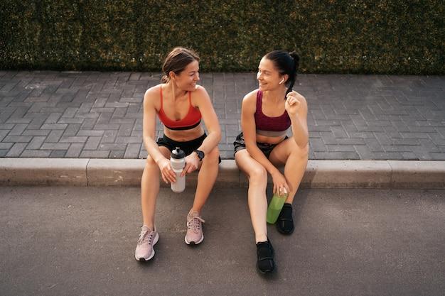 Dwie kobiety przed miejskim treningiem. dziewczyny przygotowujące się do biegania i siedzące na ulicy. przerwa fitness