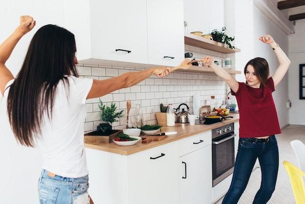 Dwie kobiety przygotowują jedzenie grać w kuchni.