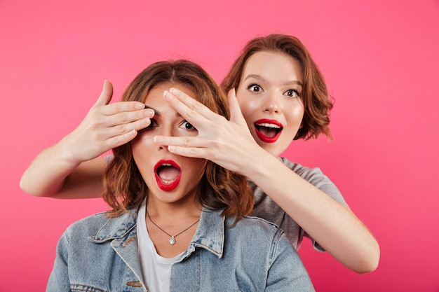 Dwie kobiety przyjaciół obejmujących oczy rękami.