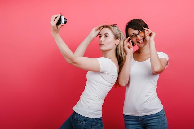 Dwie kobiety przyjaciółki pozujące w studio - zrób zdjęcie selfie, zabawny czas.