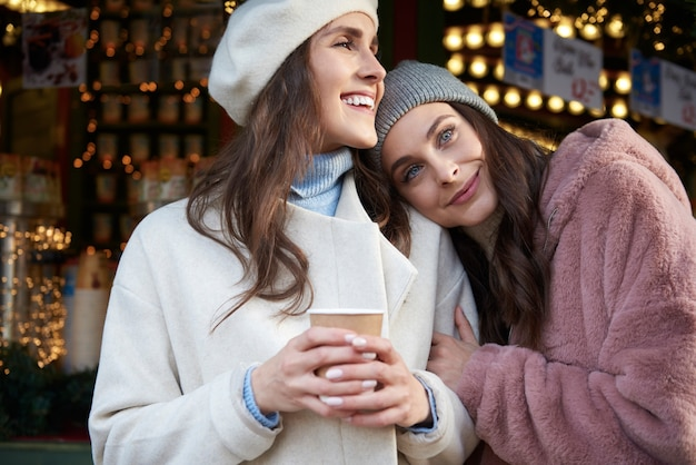 Dwie kobiety przytulanie na jarmarku bożonarodzeniowym