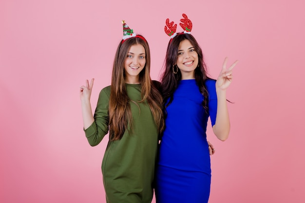 Dwie kobiety przytulanie pokazując gest pokoju z śmieszne świąteczne obręcze na głowie na białym tle nad różowym