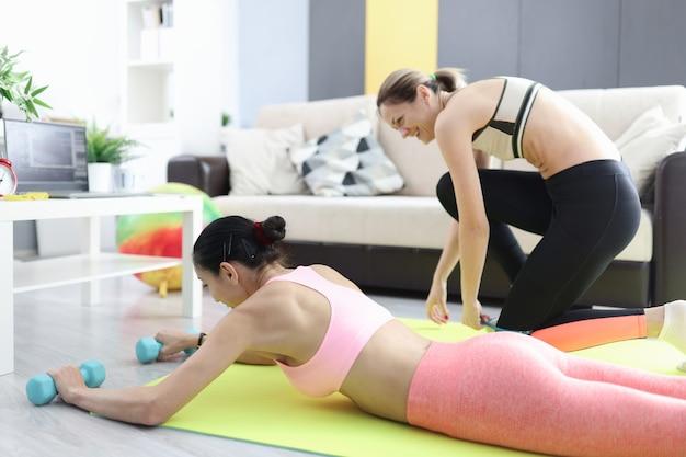 Dwie kobiety robi fitness w domu w internecie. koncepcja treningu w domu