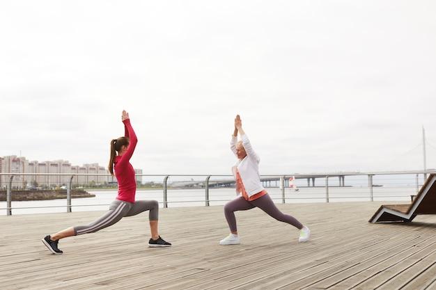 Dwie kobiety robi joga na molo