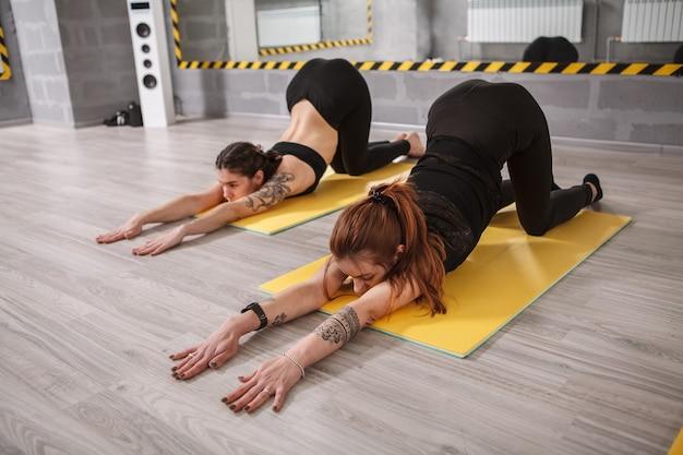 Dwie kobiety rozciągające się na zajęciach jogi w studiu sportowym