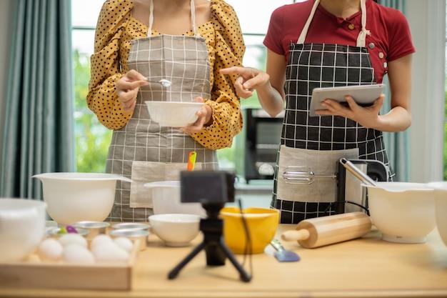 Dwie kobiety rozmawiają i przygotowują lekcję gotowania online.