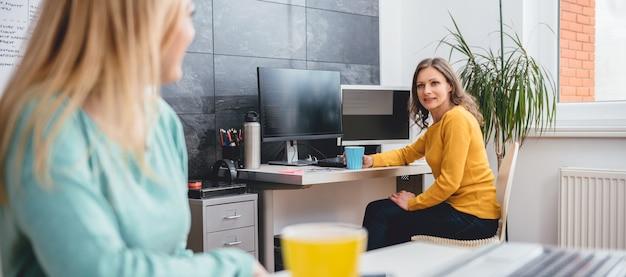 Dwie kobiety rozmawiają w biurze