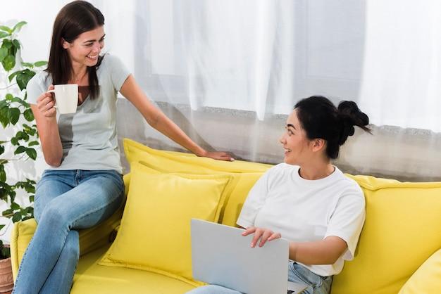 Dwie kobiety rozmawiają w domu na kanapie z kawą i laptopem
