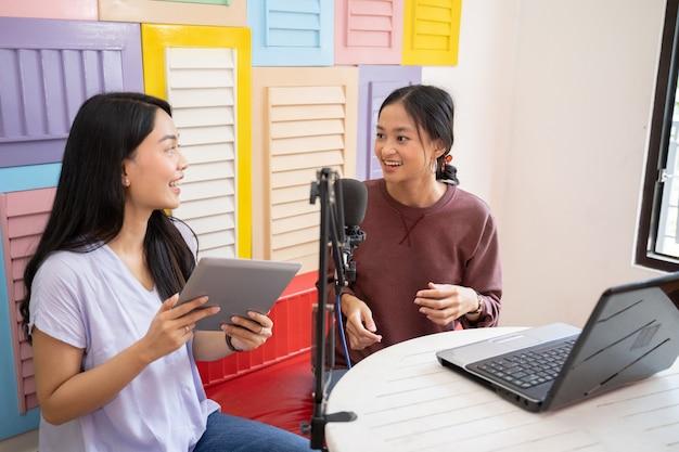 Dwie kobiety rozmawiające podczas transmisji za pomocą tabletu i laptopa przed mikrofonem