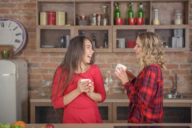 Dwie kobiety rozmawiające przy filiżance kawy w kuchni
