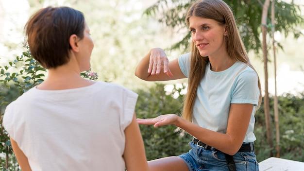 Dwie kobiety rozmawiające ze sobą przy użyciu języka migowego