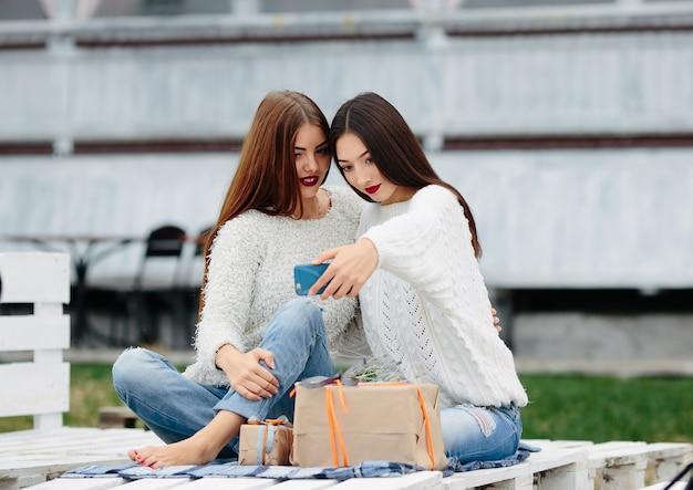 Dwie kobiety siedzą na ławce na zewnątrz i strzelają do prezentów dla smartfona