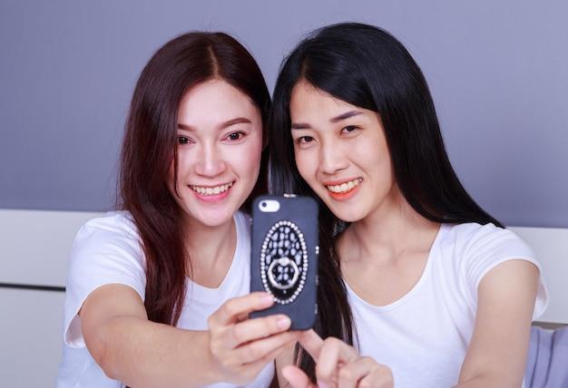 Dwie kobiety siedzą na łóżku, baw się i zrób selfie