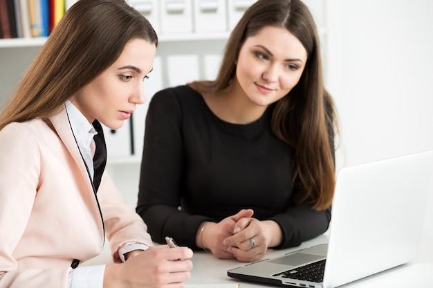 Dwie kobiety siedzą w biurze i patrząc na monitor laptopa, omawiając niektóre pytania