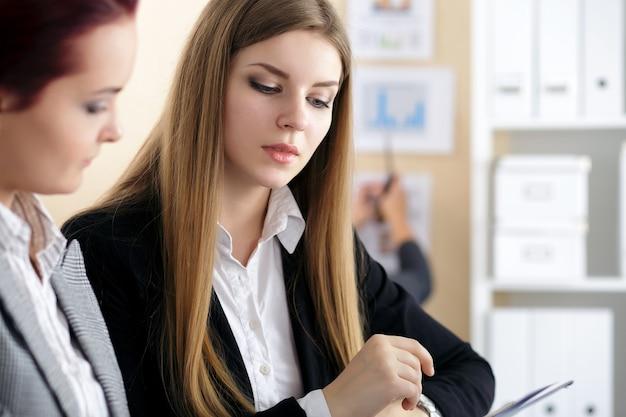 Dwie kobiety siedzące w biurze i patrząc na wykresy i tabele, omawiając niektóre pytania
