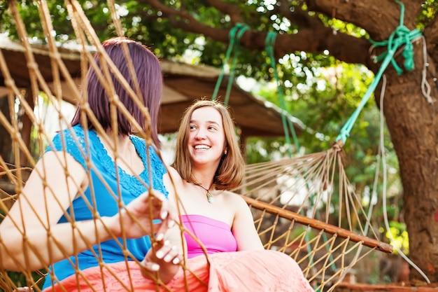 Dwie kobiety siedzące w hamaku