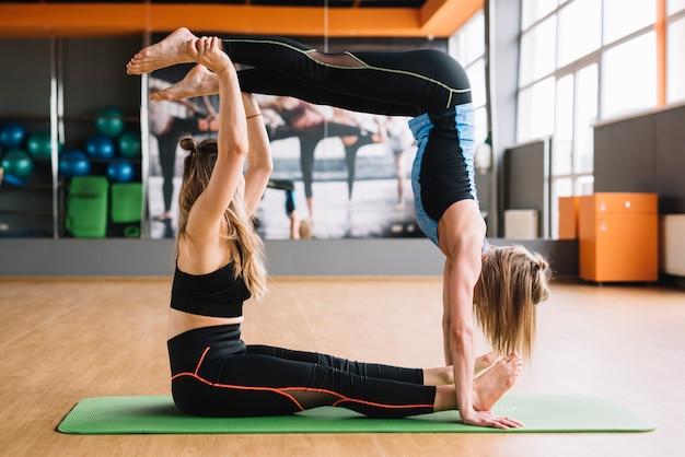 Dwie kobiety siedzącej na matę do ćwiczeń pieniący się geometryczny kwadratowy kształt
