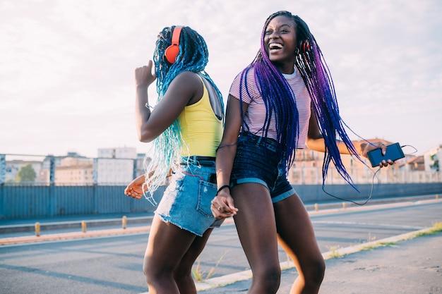 Dwie kobiety siostry na zewnątrz słuchania muzyki tańca