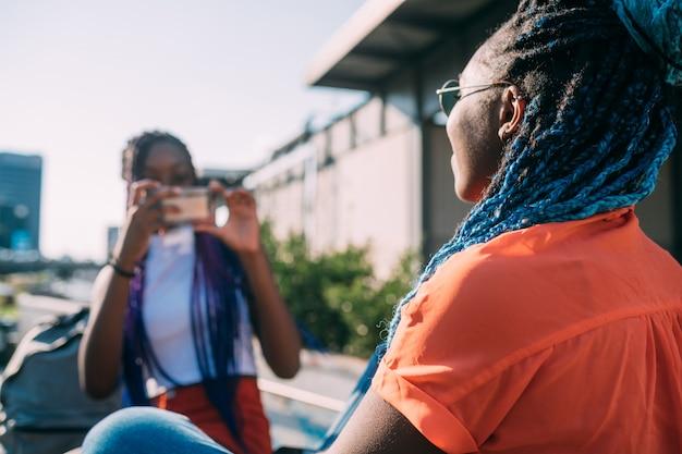 Dwie kobiety siostry na zewnątrz za pomocą smartfona robienia zdjęć