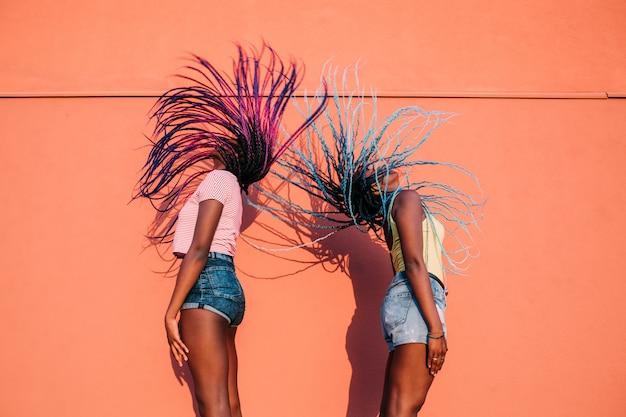 Dwie kobiety siostry tańczy włosy na zewnątrz